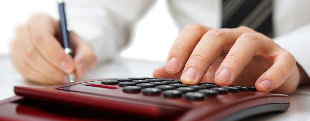 Business Man Writing and Using a Hand Calculator for Healthcare Accounting Services